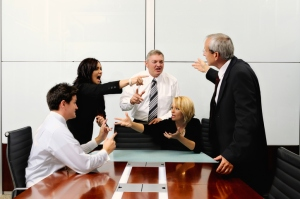 Agitated business people at a meeting pointing at each other